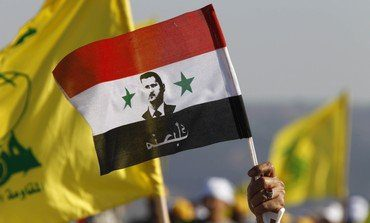 A supporter of Lebanon's Hezbollah waves a Syrian flag depicting Syria's President Bashar al-Assad as other supporters wave Hezbollah flags